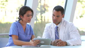 Medical Staff Review Information On Digital Tablet Stock Image