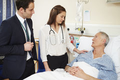 Medical Staff On Rounds Standing By Male Patient's Bed Royalty Free Stock Photos