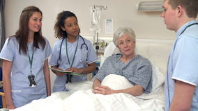Medical Staff On Rounds Standing By Male Patient's Bed
