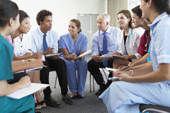 Medical Staff Seated In Circle At Case Meeting stock photography