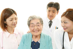 Medical staff with senior woman Stock Photography