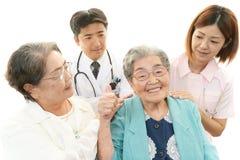 Medical staff with senior women Stock Image