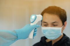 Medical staff use infrared forehead thermometer for check body temperature, Covid-19 outbreak concept