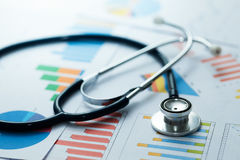 Medical statistics and graphic charts with stethoscope. On table stock photos