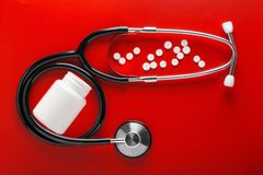 Medical stethoscope of black color and pills in jar on clean red background. Layout for the designer. Medical stethoscope of black color and pills in jar on stock photos
