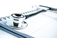 Medical stethoscope with blue tint on notebook Stock Images