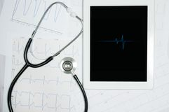 Medical stethoscope and tablet display with cardiogram chart. Stock Image