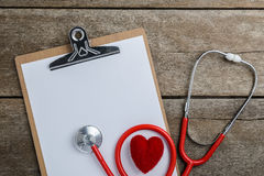 Medical stethoscope with clipboard and heart on wooden table Stock Photography