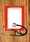 Medical stethoscope with clipboard on wooden table background Royalty Free Stock Image
