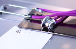 Medical stethoscope with a computer on the desk.  Royalty Free Stock Photo