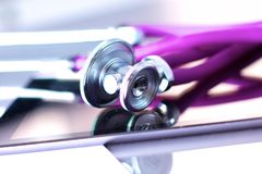 Medical stethoscope with a computer on the desk.  Stock Image