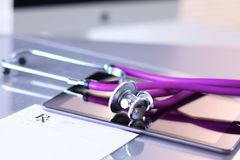Medical stethoscope with a computer on the desk.  Stock Photo