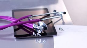 Medical stethoscope with a computer on the desk.  Royalty Free Stock Photos