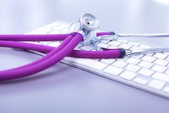 Medical stethoscope with a computer on the desk.  Royalty Free Stock Images