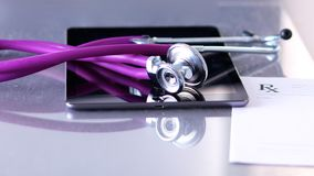 Medical stethoscope with a computer on the desk.  Stock Images