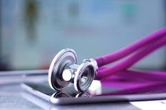 Medical stethoscope with a computer on the desk.  Stock Photos