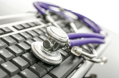 Medical stethoscope on computer keyboard Stock Photos