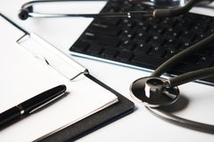 Medical stethoscope on computer keyboard with clipboard and pen royalty free stock image