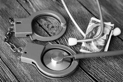 Medical stethoscope on dollar bills and handcuffs. Medical stethoscope on dollar bills, extra close up Stock Photography