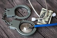 Medical stethoscope on dollar bills and handcuffs. Medical stethoscope on dollar bills, extra close up Royalty Free Stock Images