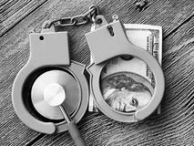 Medical stethoscope on dollar bills and handcuffs. Medical stethoscope on dollar bills, extra close up Stock Photo