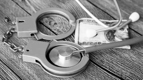 Medical stethoscope on dollar bills and handcuffs. Medical stethoscope on dollar bills, extra close up Royalty Free Stock Photography