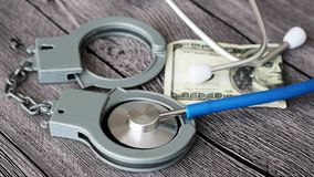 Medical stethoscope on dollar bills and handcuffs. Medical stethoscope on dollar bills, extra close up Royalty Free Stock Photos