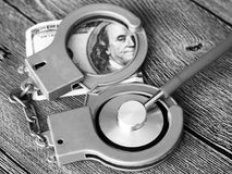 Medical stethoscope on dollar bills and handcuffs. Medical stethoscope on dollar bills, extra close up Stock Images