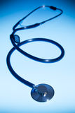 Medical stethoscope dramatically lit against a blue background Stock Photo