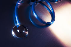 Medical stethoscope dramatically lit on a metalic table. Medical Stethoscope on a metalic background and dramatic lighting Stock Images