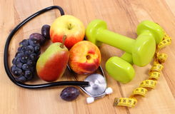 Medical stethoscope, fruits and dumbbells for using in fitness Stock Images