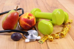 Medical stethoscope, fruits and dumbbells for using in fitness Royalty Free Stock Photo