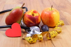 Medical stethoscope, fruits and tape measure, healthy lifestyle Stock Photo