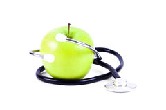 Medical stethoscope and green apples. Stock Photos