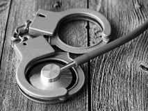 Medical stethoscope and handcuffs. Extra close up Stock Photo