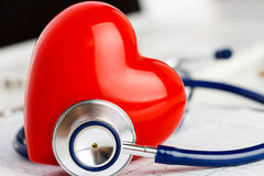 Medical stethoscope head and red toy heart. Lying on cardiogram chart closeup. Cardio therapeutist, pulse graph, cardiac physical, heart rate measure stock images