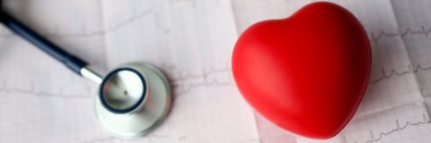 Medical stethoscope head and red toy heart. Lying on cardiogram chart closeup. Cardio therapeutist pulse graph cardiac physical heart rate measure arrhythmia royalty free stock photography