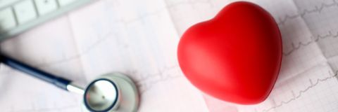 Medical stethoscope head and red toy heart. Lying on cardiogram chart closeup. Cardio therapeutist pulse graph cardiac physical heart rate measure arrhythmia royalty free stock images
