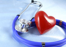 Medical stethoscope head and red toy heart lying on cardiogram chart closeup. help, prophylaxis, disease prevention or insurance c Royalty Free Stock Images