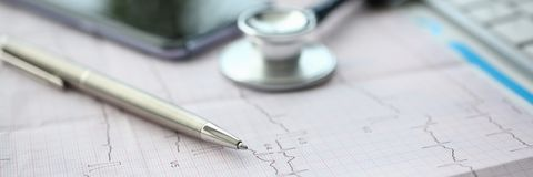 Medical stethoscope head and red toy heart. Medical stethoscope head and silver pen lying on cardiogram chart closeup. Cardio therapeutist pulse graph cardiac royalty free stock photo