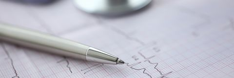 Medical stethoscope head and red toy heart. Medical stethoscope head and silver pen lying on cardiogram chart closeup. Cardio therapeutist pulse graph cardiac stock image