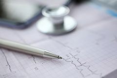 Medical stethoscope head and red toy heart. Medical stethoscope head and silver pen lying on cardiogram chart closeup. Cardio therapeutist pulse graph cardiac royalty free stock photography