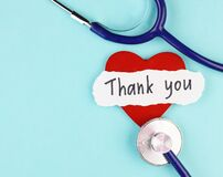 Medical stethoscope, healthy red heart and the inscription Thank you on a blue background