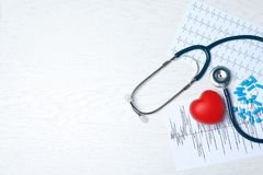 Medical stethoscope, heart, pills and cardiograms on wooden background, top view with space for text. Cardiology concept royalty free stock photo