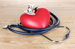 Medical stethoscope and heart on wooden Royalty Free Stock Images