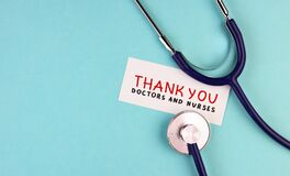 Medical stethoscope and the inscription Thank you to doctors and nurses on a blue background