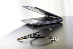 Medical stethoscope and a laptop on the table. Royalty Free Stock Photos
