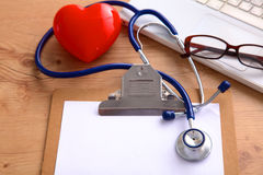 Medical stethoscope lying on a computer keyboard, documents Royalty Free Stock Images