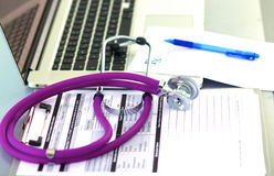 A medical stethoscope near a laptop on table, on Royalty Free Stock Photography
