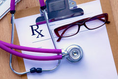 A medical stethoscope near a laptop on a wooden Stock Image